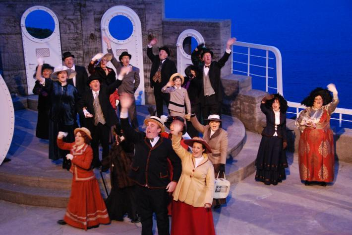 A crowd of people on the Minack stage, smiling and waving