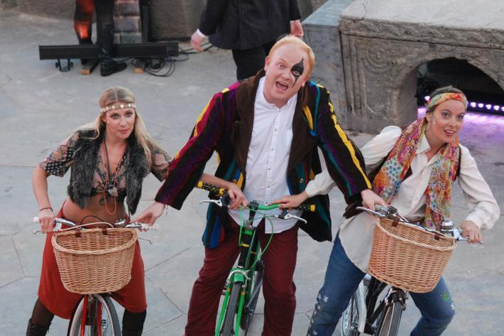 Three actors in hippie costumes riding bicycles on The Minack stage