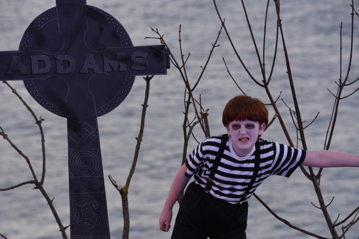 A ghoulish child snarls next to a large tombstone marked Addams