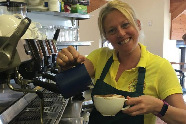 A smiling barrista serves a cup of coffee