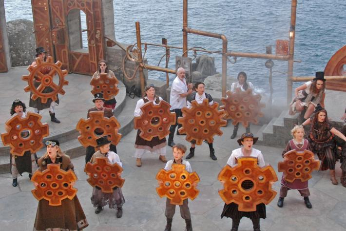 A group of actors in steam punk costumes carrying cogs and mechanical gadgets