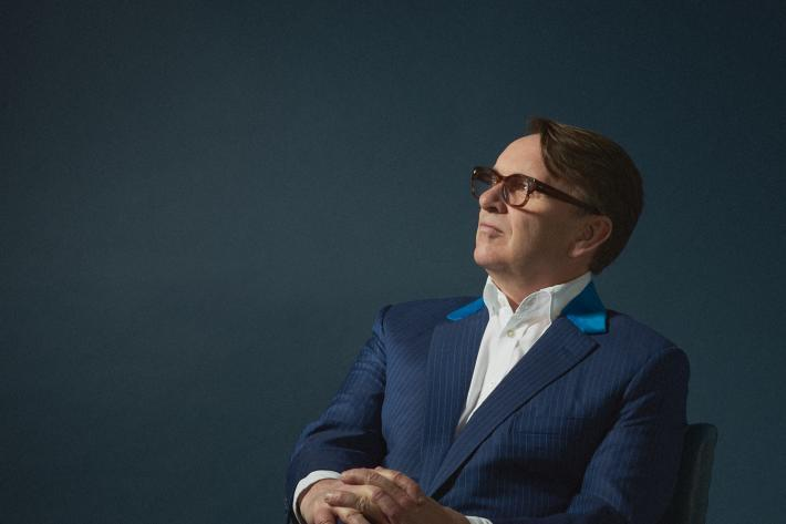 Portrait of Chris Difford in a suit and seated