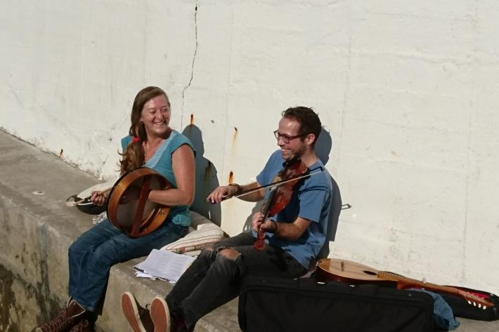 Bec Applebee and Richard Trethewey playing instruments on a seawall