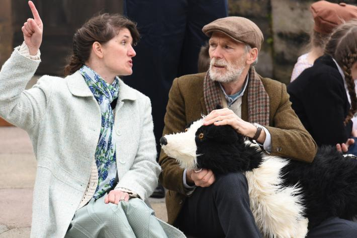 An old man sits on the stage with a life size collie puppet, talking to a woman who is gesticulating