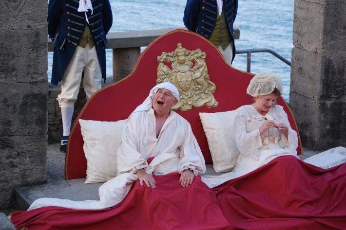 A King and Queen sit up in their royal bed on the Minack stage