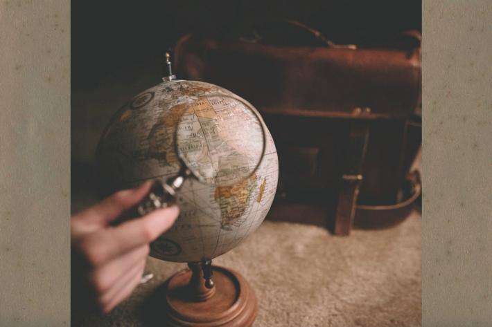 An old globe and a hand holding a magnifying glass