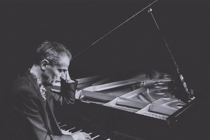 Moody black and white image of Simon Latarche at his grand piano