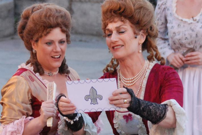 Two fashionable women in eighteenth century costyume exult over a ticket with a crest on it