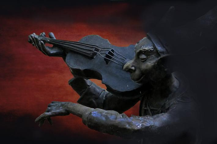 A sinister figure plays a violin silhouetted against a flaming sky.