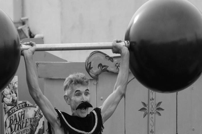 A weedy strongman lifts two enormous weights above his head.