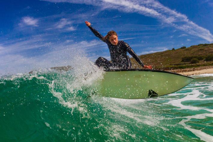 Photo of a surfer on a surging green wave