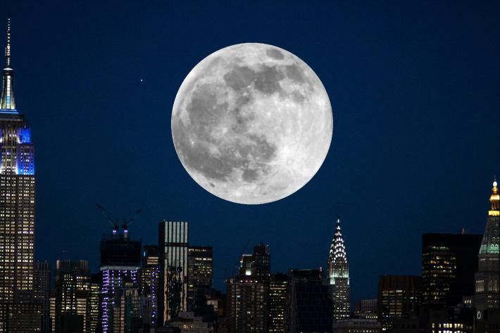 A full moon over the glittering towers of Manhattan