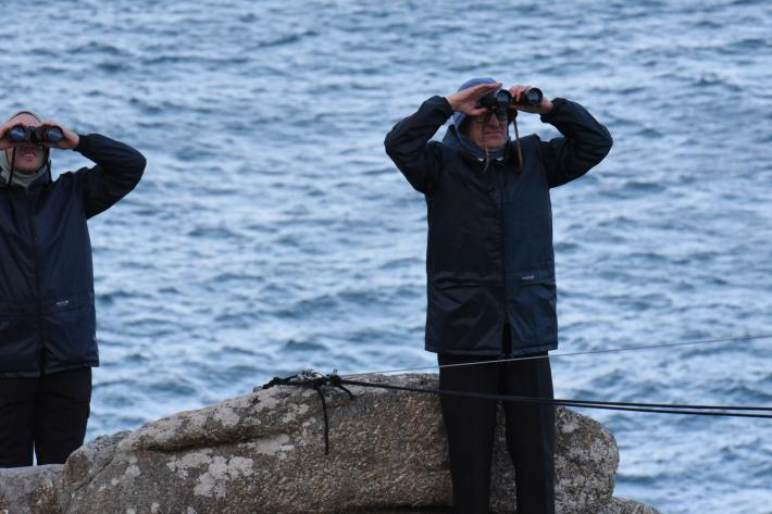 Two actors in raincoats looking through binoculars