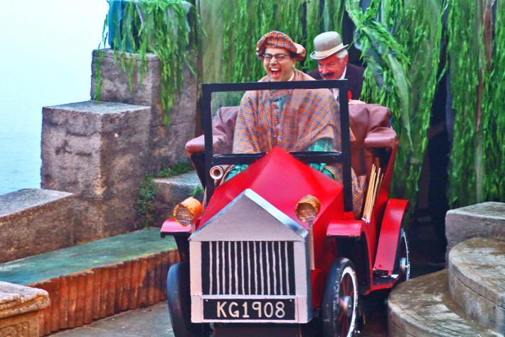 A man in a plaid coat drives a toy vintage car onto The Minack Stage, laughing delightedly