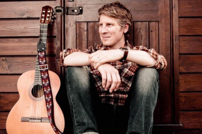 Scott Matthews sitting on a step with his guitar