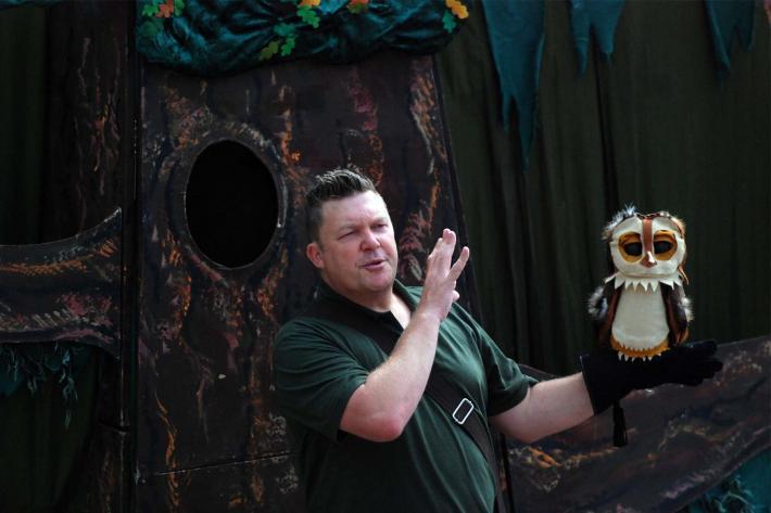 Craig Johnson holding his owl puppet during a Squashbox show